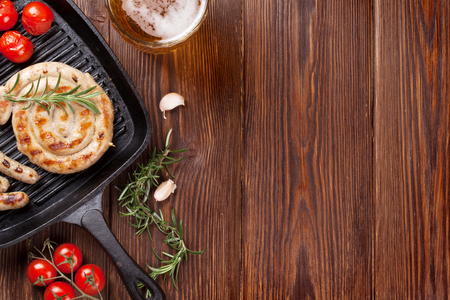 wooden table top view: Grilled sausages and beer mug on wooden table. Top view with copy space