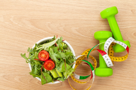 forme et sante: Dumbells, ruban à mesurer et alimentation saine sur une table en bois. Fitness et santé