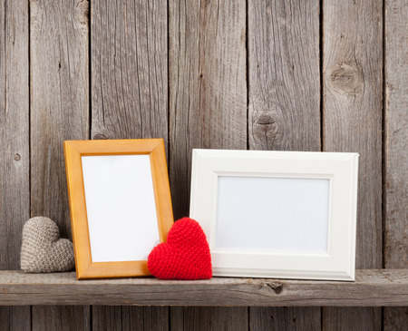 photo frame: Blank photo frames and heart presents on shelf in front of wooden wall