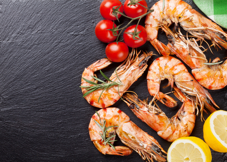 Grilled shrimps on stone plate. Top view with copy space