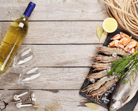 view on sea: Fresh raw sea food with spices and white wine on wooden table background. Top view with copy space Stock Photo