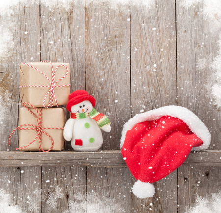 snowman wood: Christmas gift boxes, santa hat and snowman toy in front of wooden wall with copy space Stock Photo