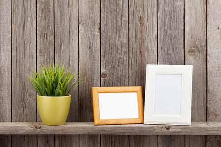 white table: Blank photo frames and plant on shelf in front of wooden wall