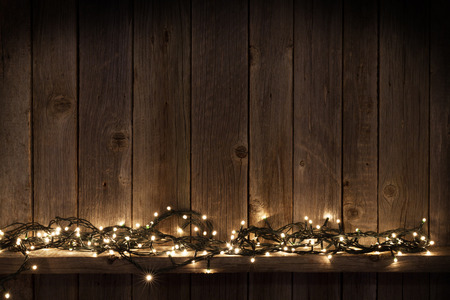 Christmas lights on shelf in front of wooden wall with copy space