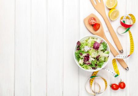 salad bowl: Fresh healthy salad, utensils and tape measure over white wooden table. View from above with copy space