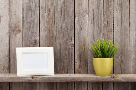 Blank photo frame and plant on shelf in front of wooden wall