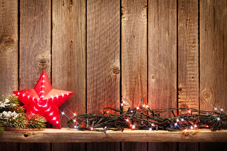 Christmas lights and star decor in front of wooden wall. View with copy space