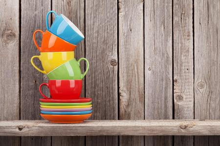apilar: las tazas de café coloridas en el estante contra la pared de madera rústica con espacio de copia Foto de archivo