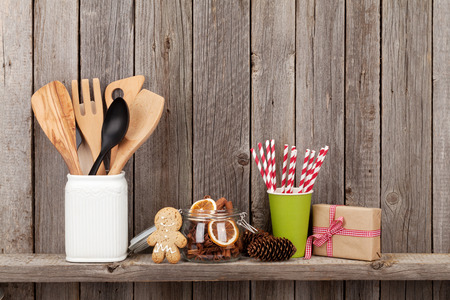 Kitchen utensils and christmas spices on shelf against rustic wooden wall with copy space