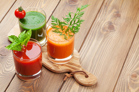 orange juice glass: Fresh vegetable smoothie on wooden table. Tomato, cucumber, carrot. View with copy space