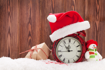 winter season: Christmas gift box, snowman toy and alarm clock in snow. View with copy space Stock Photo
