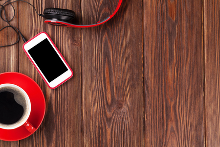 telephone cable: Smartphone, headphones and coffee cup over rustic wooden table. Top view with copy space