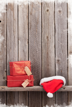 shelf ice: Christmas gift boxes and santa hat in front of wooden wall. View with copy space Stock Photo