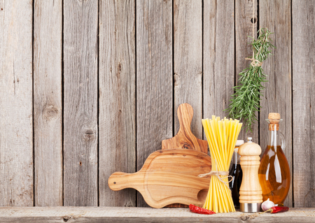 home cooking: Kitchen cooking utensils and spices on shelf against rustic wooden wall with copy space Stock Photo