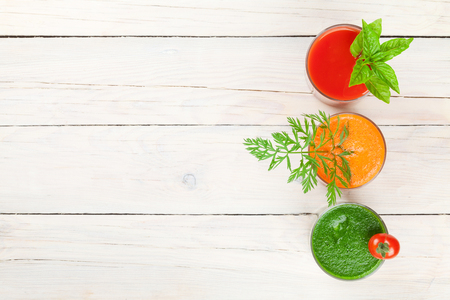 vegetables on white: Fresh vegetable smoothie on wooden table. Tomato, cucumber, carrot. Top view with copy space