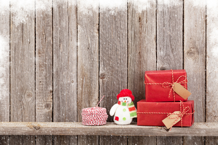 copy christmas: Christmas gift boxes and snowman toy in front of wooden wall. View with copy space Stock Photo