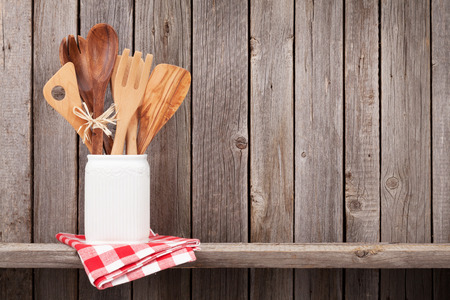 Kitchen cooking utensils on shelf against rustic wooden wall with copy space