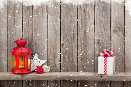 lantern: Christmas candle lantern, gift box and decor in front of wooden wall with copy space