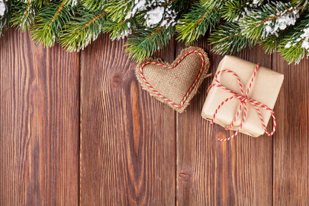 christmas gift box: Christmas tree branch with snow, gift box and heart toy on wooden table. View with copy space