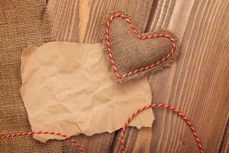 old paper: Blank old piece of paper and vintage handmaded valentines day toy heart over wooden background