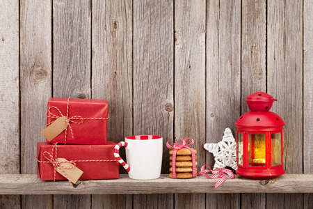 christmas decor: Christmas candle lantern, gift boxes and decor in front of wooden wall with copy space