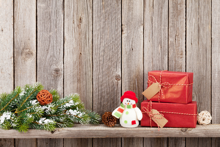 snowman wood: Christmas gift boxes and snowman toy in front of wooden wall. View with copy space Stock Photo