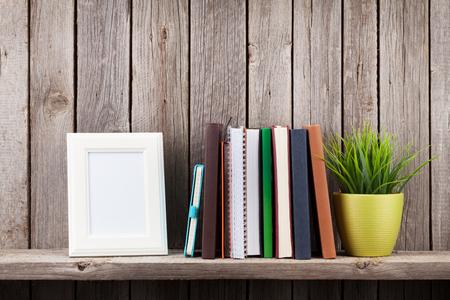 Houten plank met fotolijsten, boeken en plant op de voorgrond van de houten wand. Weergave met kopie ruimte