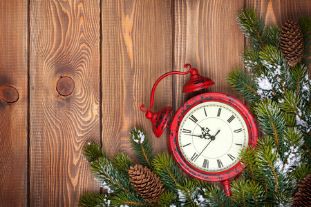 clock: Christmas wooden background with clock, snow fir tree and copy space Stock Photo