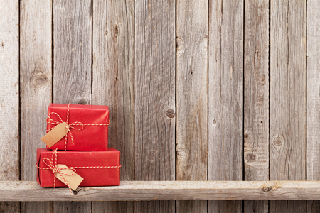 Christmas gift boxes in front of wooden wall. View with copy space