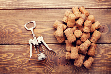 cork: Wine corks and corkscrew over rustic wooden table background. Top view