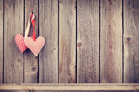 wood texture: Two Valentines day hearts on rustic wooden wall with copy space. Toned Stock Photo