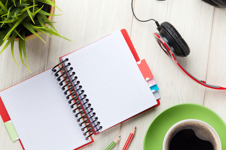 papel de notas: Office wooden desk with notepad, coffee cup and headphones. Top view with copy space