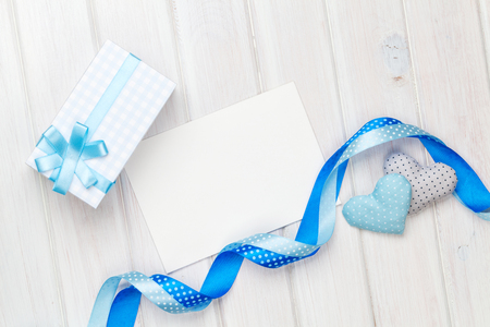 blue green background: Photo frame or greeting card and handmaded valentines day toy hearts over white wooden background