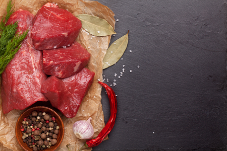 red food: Raw fillet beef steak and spices on stone board. Top view with copy space