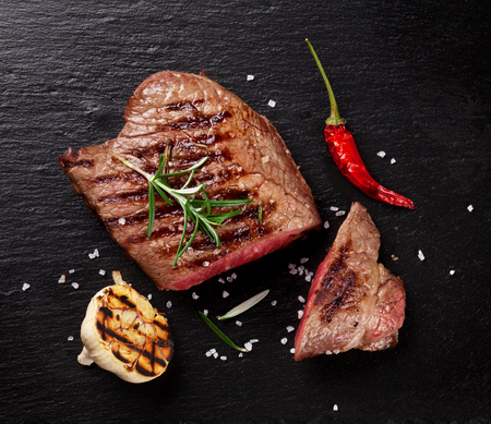 beef cuts: Grilled beef steak with rosemary, salt and pepper on black stone plate. Top view Stock Photo
