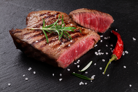 cut: Grilled beef steak with rosemary, salt and pepper on black stone plate
