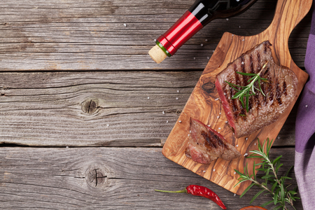 chili: Grilled beef steak with rosemary, salt and pepper and wine bottle on wooden table. Top view with copy space
