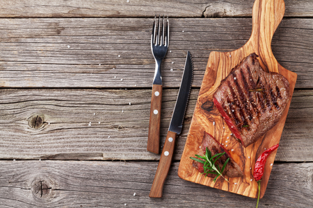 cut: Grilled beef steak with rosemary, salt and pepper on wooden table. Top view with copy space