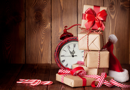 Christmas gift boxes, alarm clock and santa hat. View with copy space
