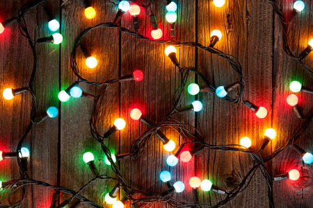 light to dark: Christmas colorful lights on wooden table