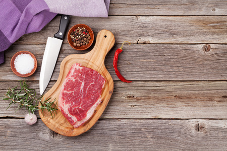 Raw Meat: Raw beef steak and spices on wooden table. Top view with copy space