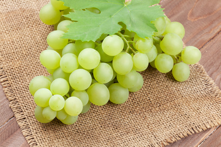 grape: Bunch of white grapes with leaves over burlap napkin
