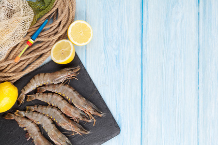 prawn: Fresh raw tiger prawns and fishing equipment on wooden table. Top view with copy space Stock Photo