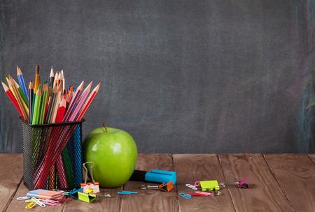 Školní a kancelářské potřeby na stole ve třídě před tabulí. Zobrazení s kopií vesmíru