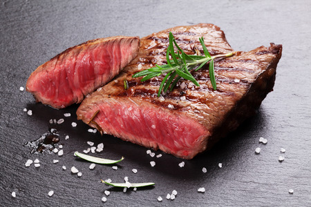 rare: Grilled beef steak with rosemary, salt and pepper on black stone plate