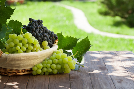 Red and white grapes in basket on garden table