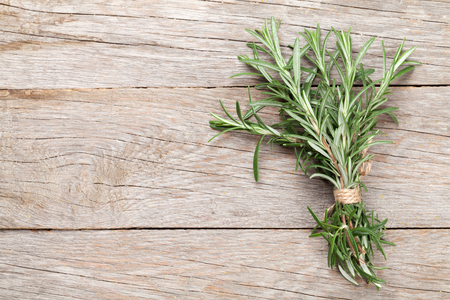 Fresh garden rosemary on wooden table. Top view with copy space