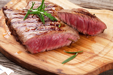 Grilled beef steak with rosemary, salt and pepper on wooden board