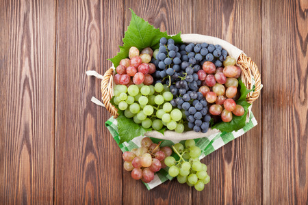 Bunch of red, purple and white grapes in basket on wooden table background. Top view