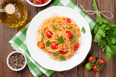 Spaghetti pasta with tomatoes and parsley on wooden table. Top view Imagens